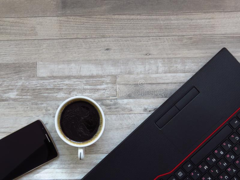Office desk with black laptop, golden colour mobile phone, a cup of coffee. Business. Success. Coffee break. Office work. Top view stock photography