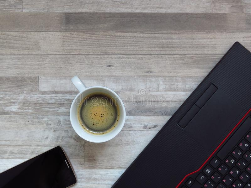 Office desk with black laptop, golden colour mobile phone, a cup of coffee. Business. Success. Coffee break. Office work. Top view royalty free stock photo