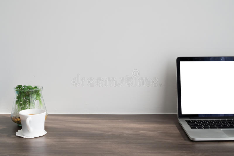 Office desk with blank screen on laptop, fresh coffee cup, dwarf royalty free stock images