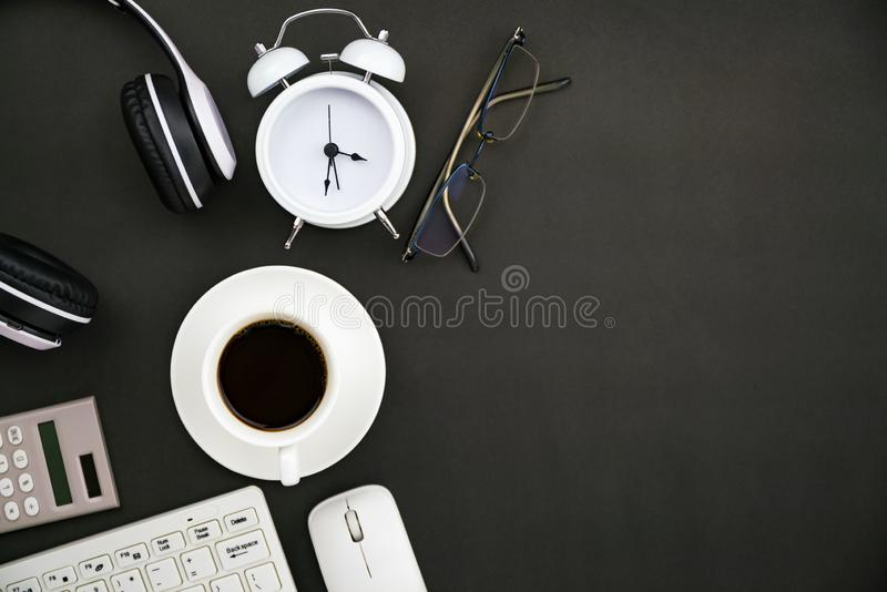 Office desk business objects of white coffee cup,keyboard,headphone,white alarm clock,calculator,mouse and glasses on blackboard.  stock photography