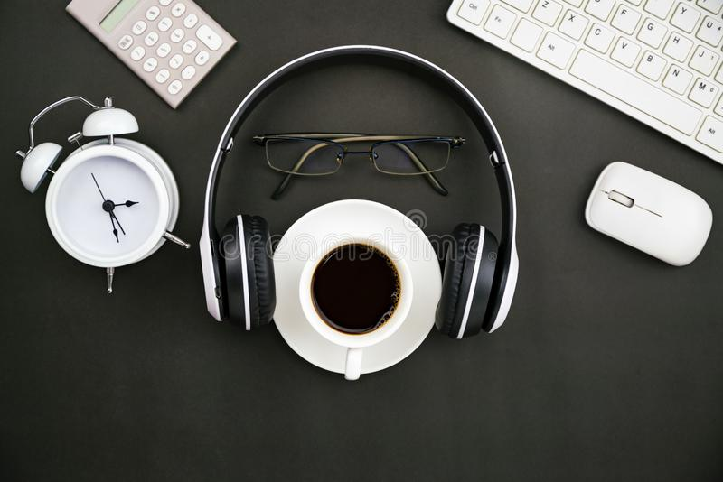 Office desk business objects of white coffee cup,keyboard,headphone,white alarm clock,calculator,mouse and glasses on blackboard.  royalty free stock images