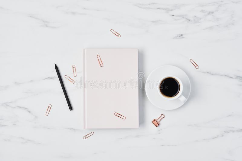 Office desk with coffee cup and pink diary stock photography
