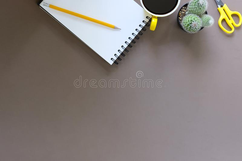 Office desk coffee cup and pencil with notepad paper on brown ta royalty free stock photos