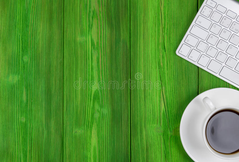 Office desk with copy space. Digital devices wireless keyboard and mouse on green wooden table with cup of coffee, top view royalty free stock photography