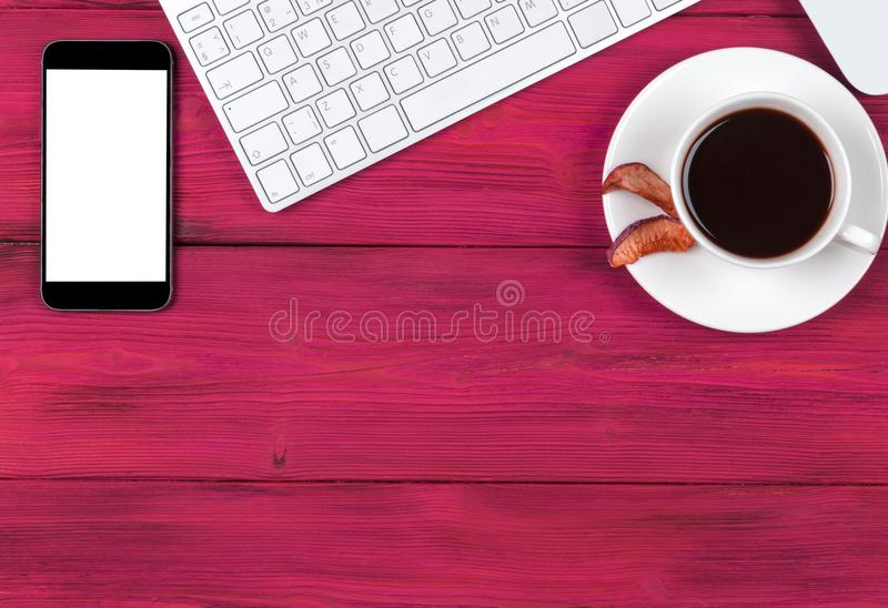Office desk with copy space. Digital devices wireless keyboard, mouse smartphone with empty screen on pink wooden table, top view. royalty free stock photo