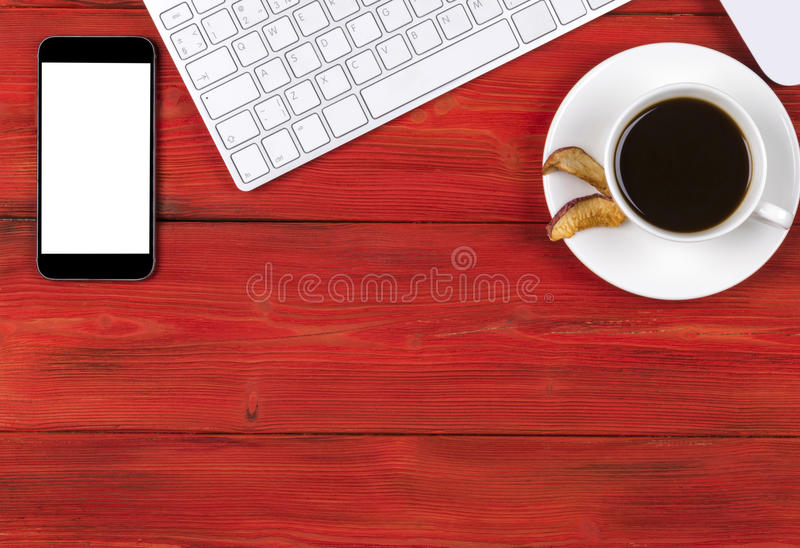 Office desk with copy space. Digital devices wireless keyboard, mouse smartphone with empty screen on red wooden table, top view stock image