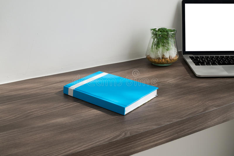 Office desk with cover blue book , blank screen on laptop, garden tree on pot and cement wall background. Concept of business lifestyle royalty free stock images