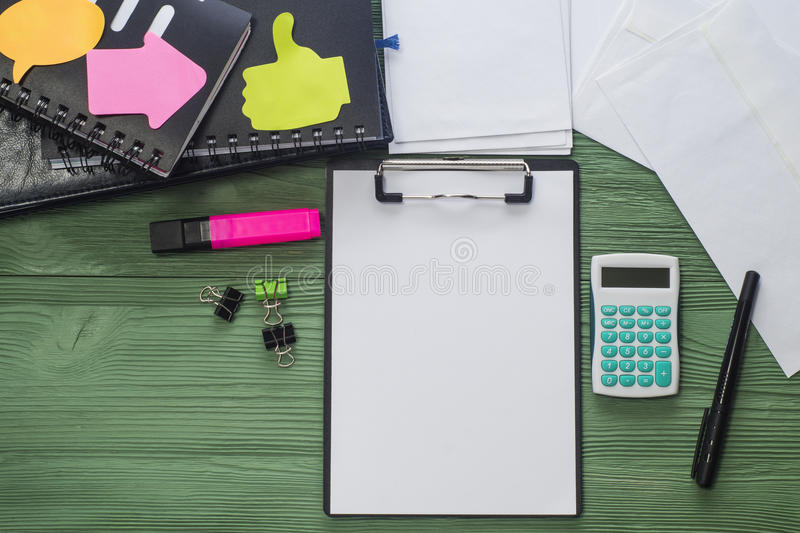 Office desk, flat lay. Workplace with folder with a blank sheet of paper, notepads and other office supply on a desk with copy space, top view. Blank template royalty free stock images