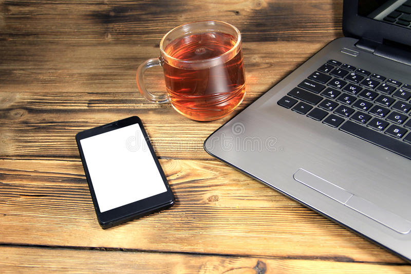 Office desk with laptop computer, smart phone and cup of tea royalty free stock photo
