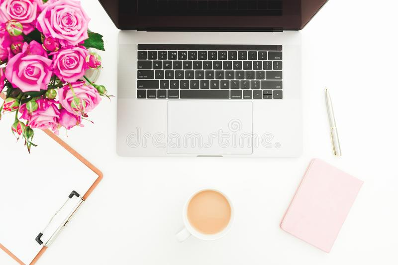 Office desk with laptop, pink roses bouquet, coffee mug, pink diary on white background. Flat lay. Top view royalty free stock image