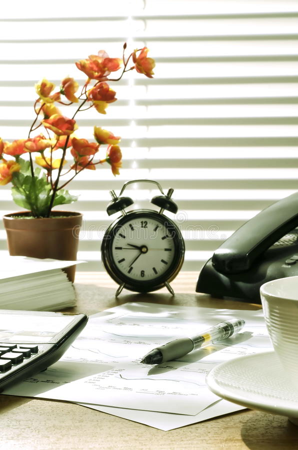 Office desk at morning. Business still life. Office desk shot under warm morning light. Conceptual shot of office and paper work, time, or work efficiency royalty free stock photo