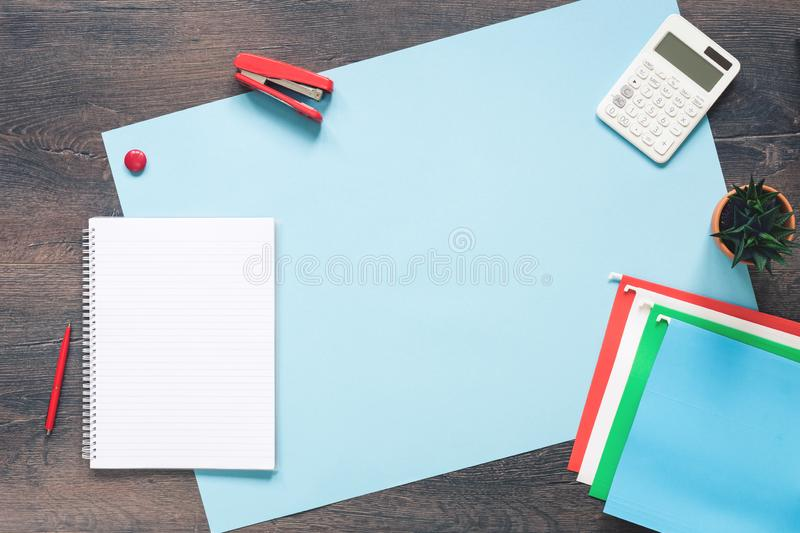Office desk with paper folders on blue. Wooden desk with documents folders notepad, calculator and cactus. Office concept flat lay with copy space stock image
