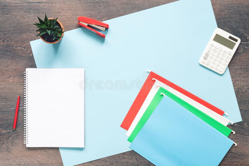 Office desk with paper folders on blue. Wooden desk with documents folders notepad, calculator and cactus. Office concept flat lay with copy space royalty free stock images