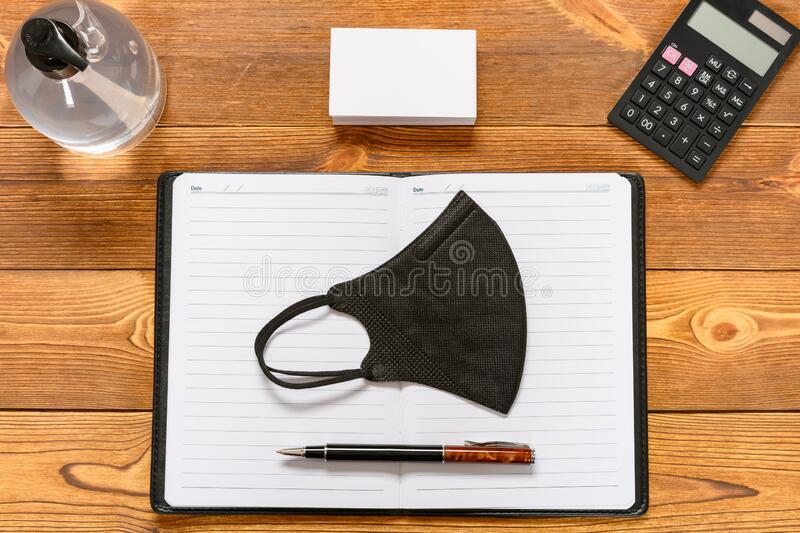 Office desk with safety mask & instant hand sanitizer concept of avoiding attack of infectious disease in the office royalty free stock images