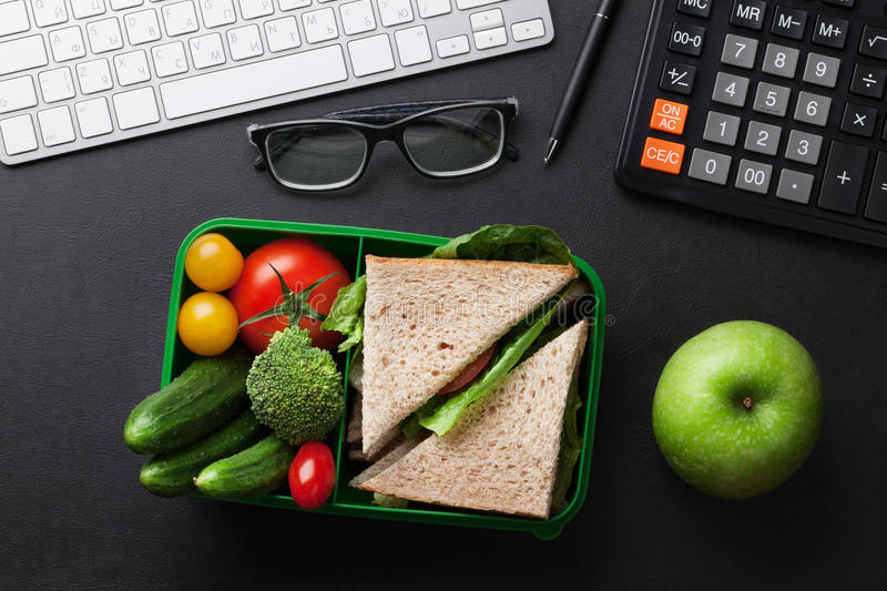 Office desk with supplies and lunch box royalty free stock photos