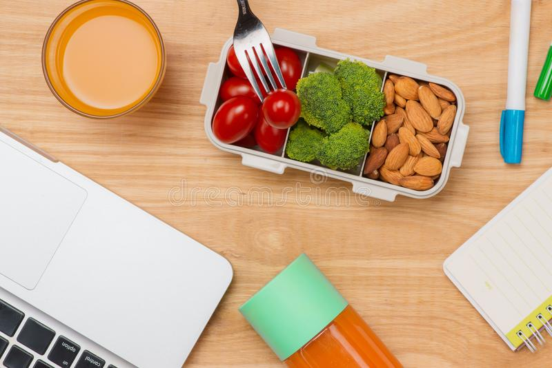 Office desk with supplies and lunch box with vegetables and almond. Top view with space for your text royalty free stock photography