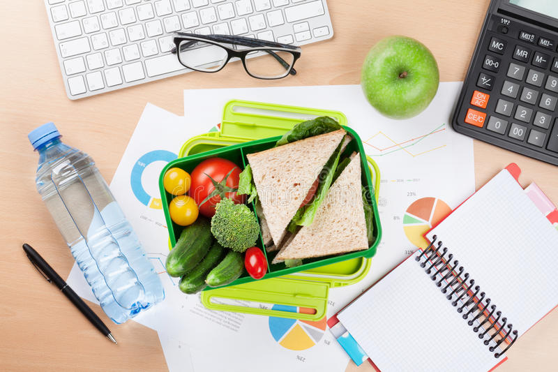 Office desk with supplies and lunch box royalty free stock photography
