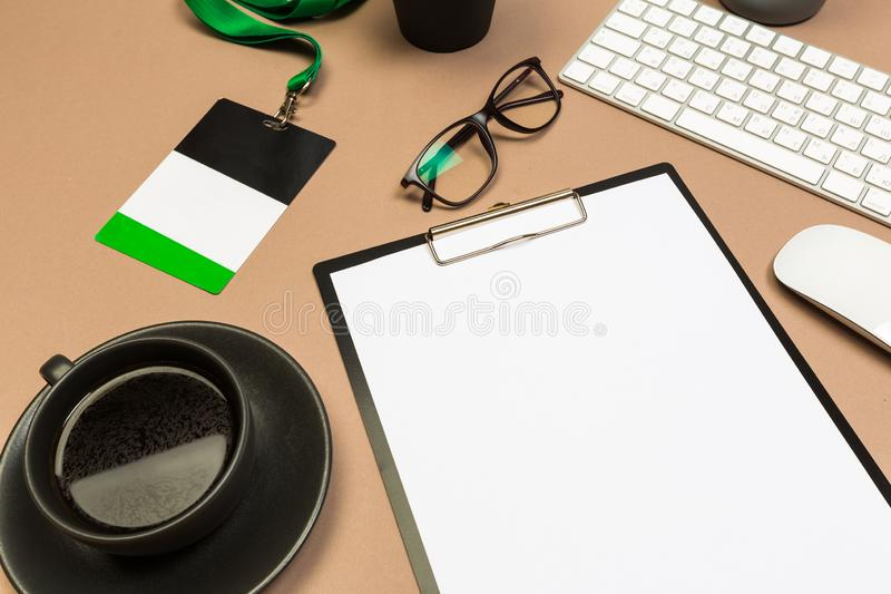Office desk table with  clipboard keyboard glasses succulent badge and coffee cup. Mock up template . Top view stock image