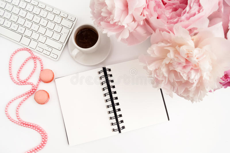 Office desk table with computer, cup of coffee and peony flowers. White wooden background. stock photography
