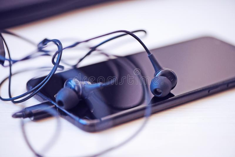 Office desk table with computer, smartphone and headphones. Essential items black color on light desk. Workplace concept. Office desk table with computer royalty free stock photos