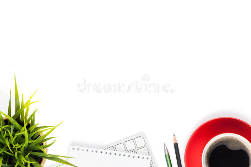 Office desk table with computer, supplies, coffee cup and flower. Isolated on white background. Top view with copy space stock photo