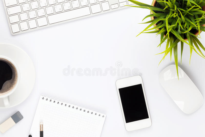 Office desk table with computer, supplies, flower and coffee cup. Top view with copy space stock photo
