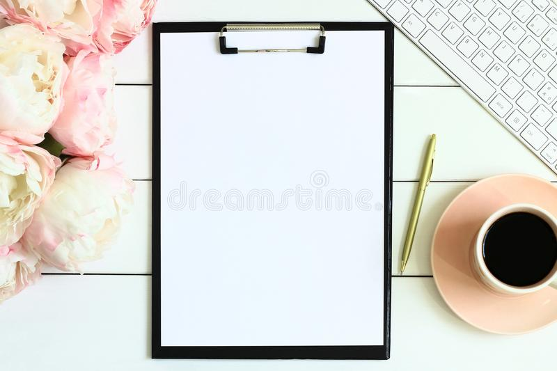 Office desk table with cup of coffee, pink peony flowers, golden pen, blank paper and clipboard. stock photo