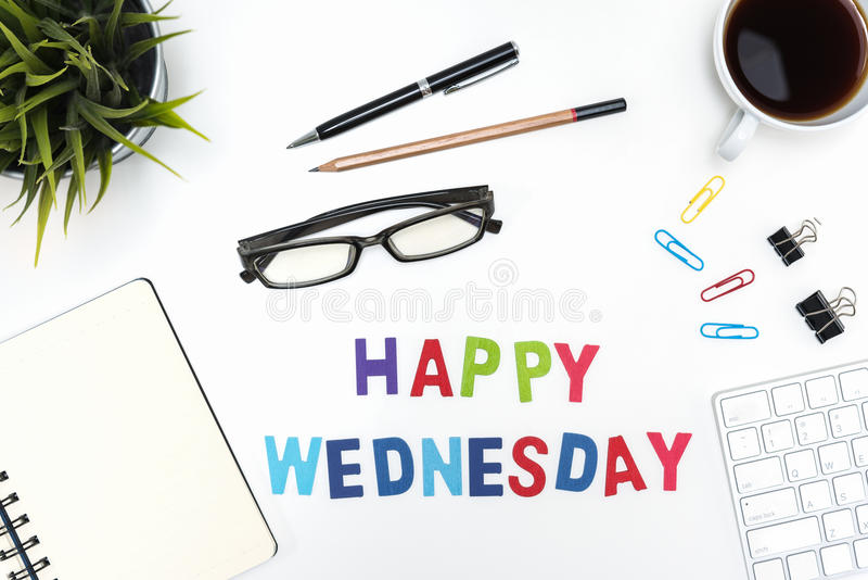 Office desk table with happy wednesday word. Office desk table with supply, pen, pencil, notebook, computer, eye glasses, sticky note, cup of coffee and happy stock image