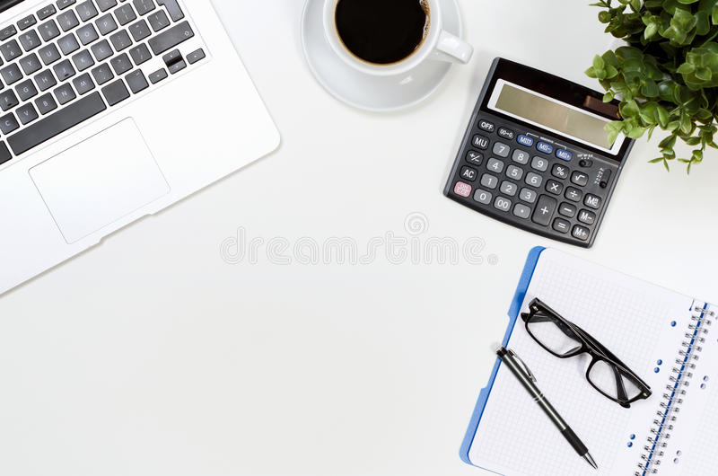 Office desk table with laptop, coffee cup and supplies top view stock photo