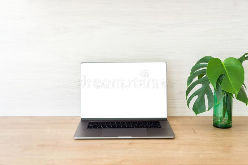 Office desk table with laptop computer with blank screen mockup and monstera plant on wooden surface. Minimal style workplace. Concept stock photography