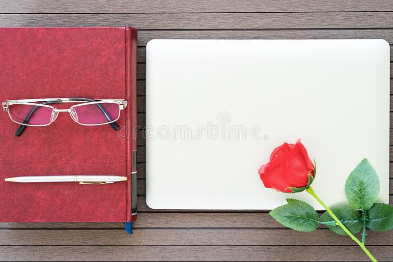 Office desk table with laptop,notebook,red rose. Top view with copy space valentine`s day, Office desk table with laptop,notebook, red rose,eye glasses royalty free stock photo