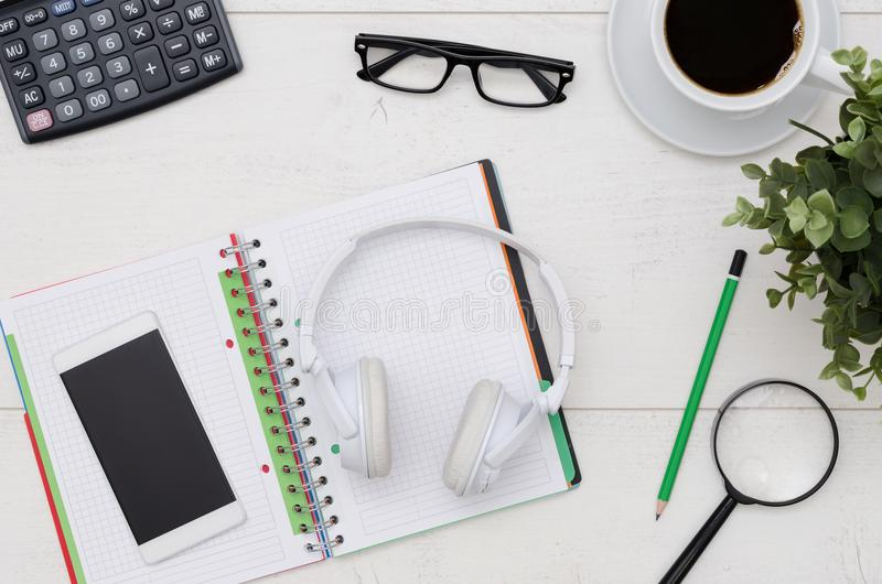 Office desk table layout with headphones and supplies stock image