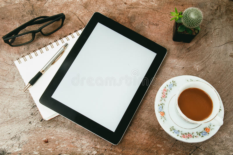 Office desk table with notebooks,tablet, pen and a cactus royalty free stock images