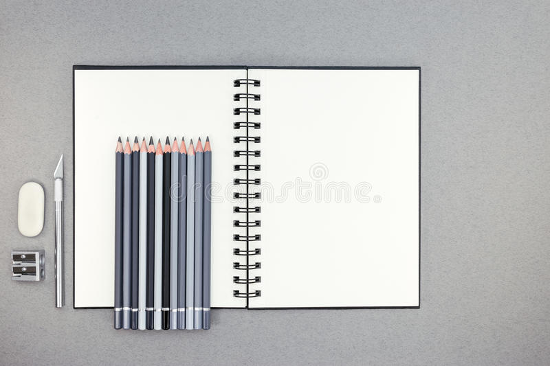 Office desk table with open spiral notebook, pencils, eraser, kn royalty free stock photography