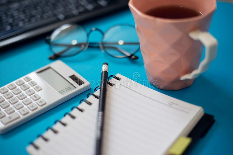 Office desk table with other supplies. Notepad with black pencil and calculator near cup of tea, glasses and keyboard of. PC stock photo