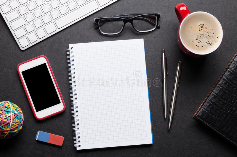 Office desk table with pc, notepad, glasses, coffee and phone. Office leather desk table with pc, notepad, glasses, coffee and smartphone. Top view with copy stock image