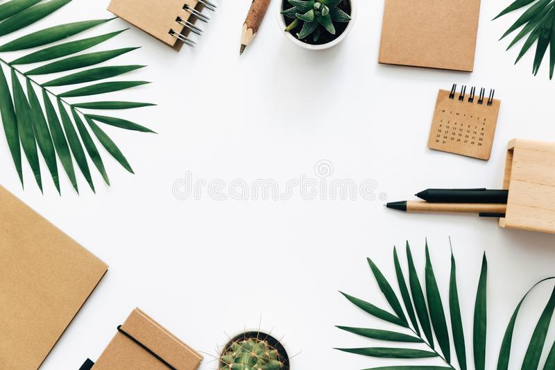 Office desk table with stationery set, supplies and palm leaves. Top view with copy space, creative flat lay royalty free stock images