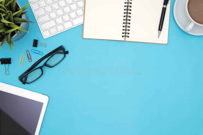 Office desk table with supplies and computer on blue background stock photography
