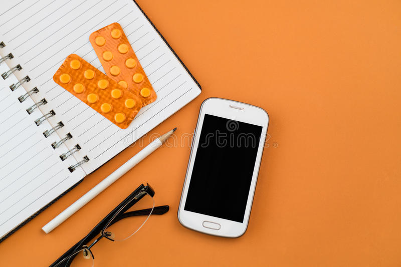 Office desk table with white smart phone,blank spiral notebook, black glasses ,white pencil and orange blisters stock images