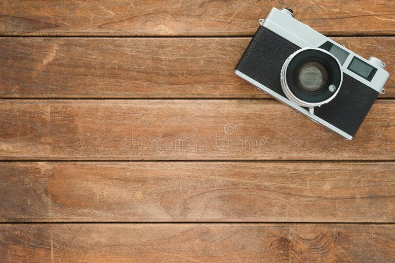 Office desk wooden table with old camera. Top view with copy space. Top view of old camera over wooden table. Retro vintage filter stock photography