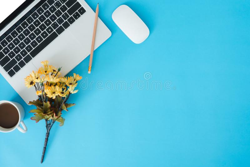 Flat lay top view copy space of a working desk with white laptop, coffee cup, supplies and decoration on blue pastel space. stock images