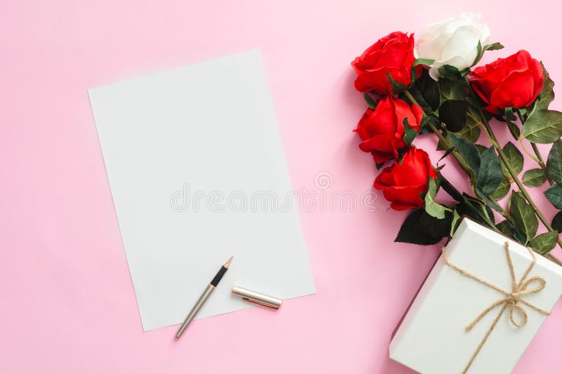 Flat lay top view mock up photo of a working space with white blank notebook, pen and valentine decoration on pink pastel. royalty free stock photos