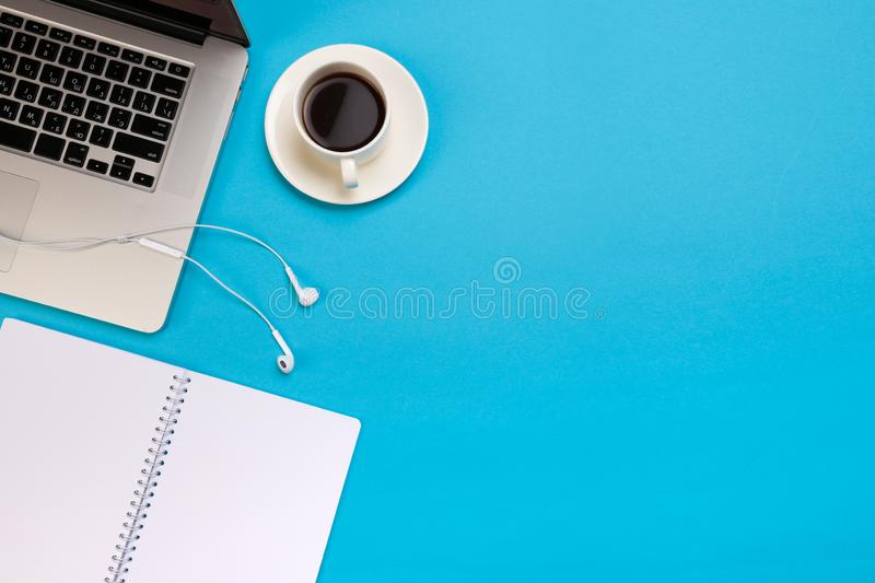 Office desk working space - Flat lay top view mockup photo of a working space with laptop, coffee cup and smartphone on blue stock photography