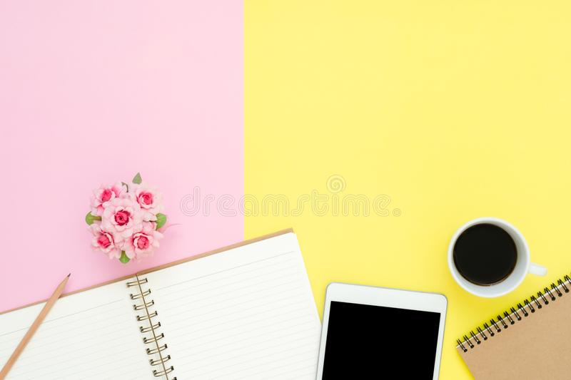 Flat lay top view photo of working space with blank mock up tablet, coffee cup and notebook on pastel background. stock photo