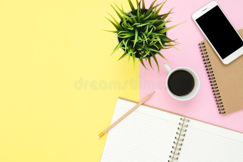 Flat lay top view of a working space with white blank notebook page, coffee cup and mock up phone on pastel background. royalty free stock photo