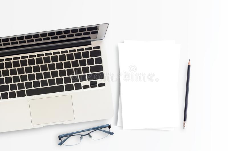Office desk or workspace with laptop computer,white paper,pencil and glasses with copy space stock images