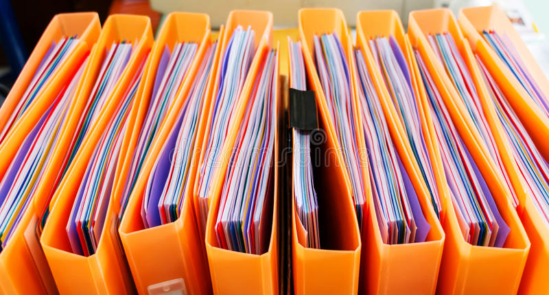 Office documents in folders. Row of orange folders with office documents inside royalty free stock photography