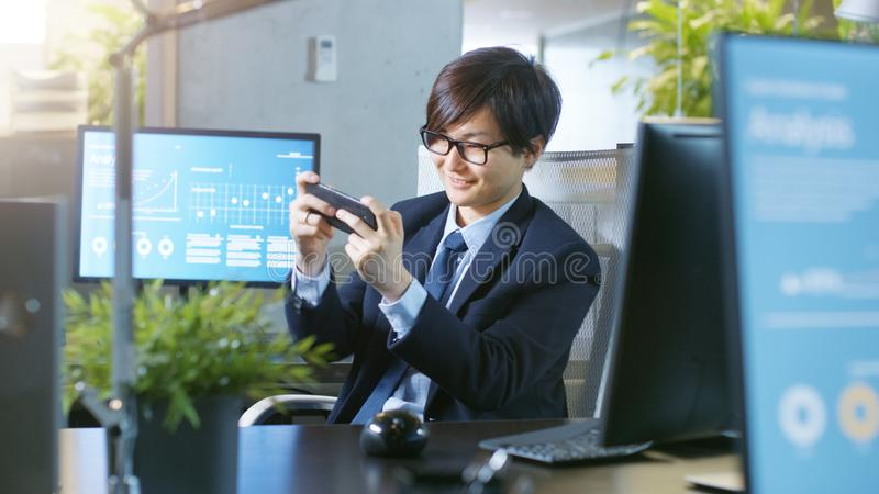 In the Office East Asian Businessman Plays Video Games on His Sm royalty free stock images