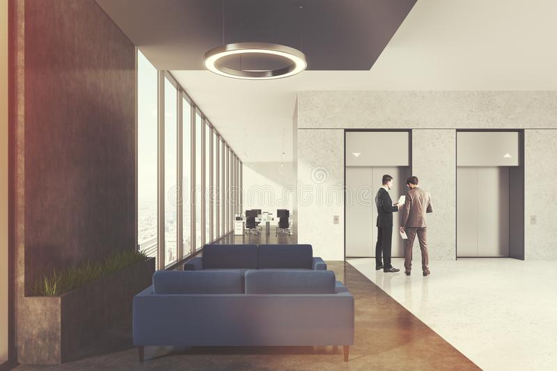 Waiting area in office, elevators, people close up. Office elevator hall with a waiting area, dark blue sofas, loft windows and round lamps. An open space room stock image