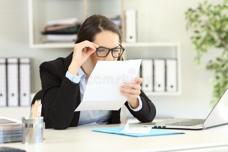 Office employee having eyesight problems. Office employee wearing eyeglasses with bad graduation having eyesight problems reading a letter stock image